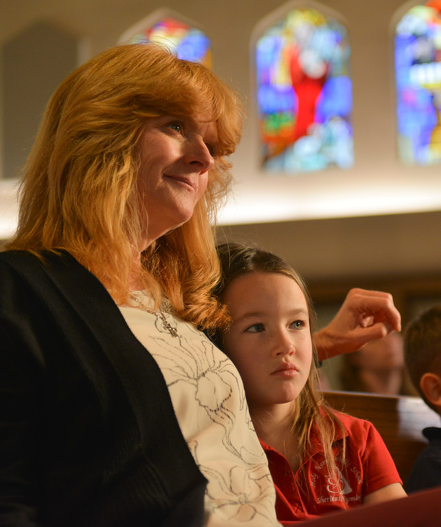 "Justin Sheely | The Sheridan Press<br /> Pre-kindergarten teacher Lori Clark sits with Ellianna Wells during the nativity program ""Through a Child's Eyes"" at Holy Name Catholic Church Wednesday, Dec. 20, 2017."