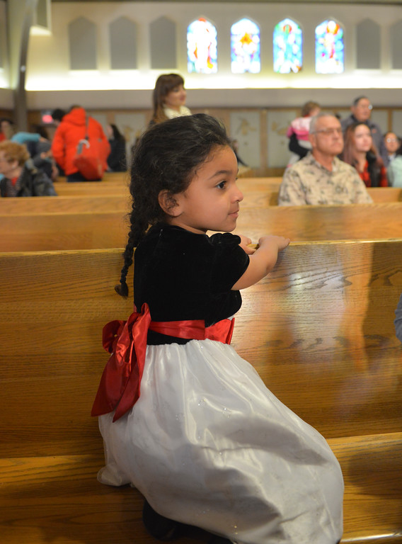 "Justin Sheely | The Sheridan Press<br /> Pre-kindergartener Amaya Franklin plays on the pew during the nativity program ""Through a Child's Eyes"" at Holy Name Catholic Church Wednesday, Dec. 20, 2017."