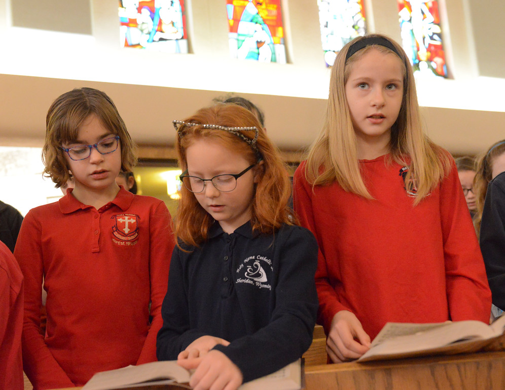 "Justin Sheely | The Sheridan Press<br /> Third-graders, from left, Anna McGarvin, Katie Harper and Jocelyn Swamy sing during the nativity program ""Through a Child's Eyes"" at Holy Name Catholic Church Wednesday, Dec. 20, 2017."