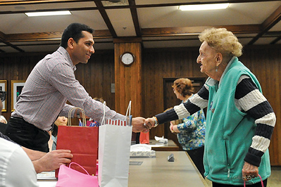 Tibby McDowell | The Sheridan Press<br /> Jins Ulahannan from India receives a gift bag from Inez Oliver Monday, Feb. 26, 2018.