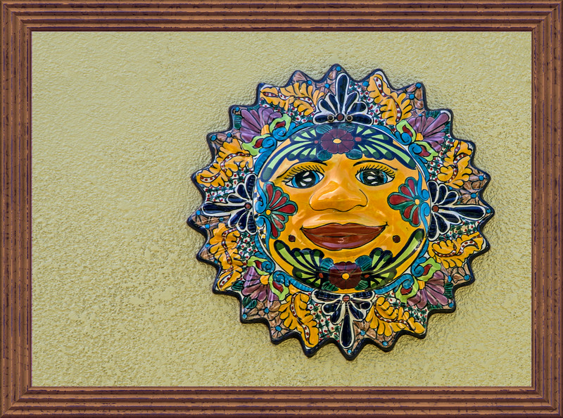 Colorful pottery star-burst face for an outside wall