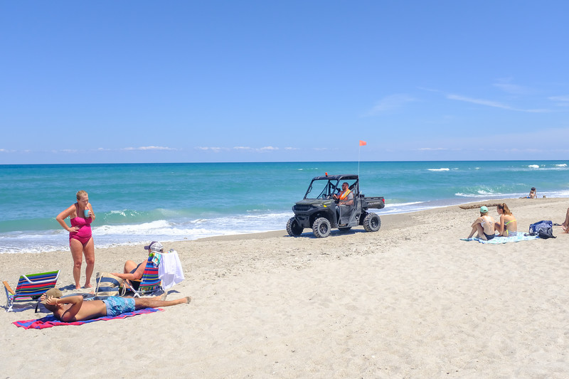 A person in an all-terrain vehicle is keeping an eye on all the people on our beach.