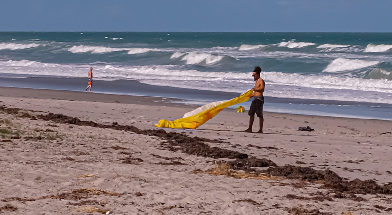 The guy was recovering his downed glider kite.