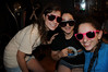 3 girls looking cool in shades, at night, indoors.