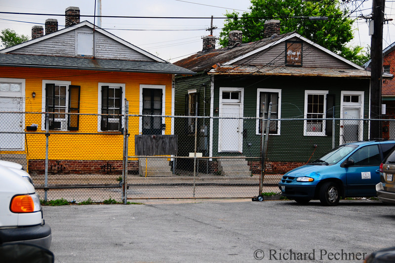 """View looking out to the street from our """"secured"""" parking lot with the familiar """"yellow"""" and """"green"""" houses."""