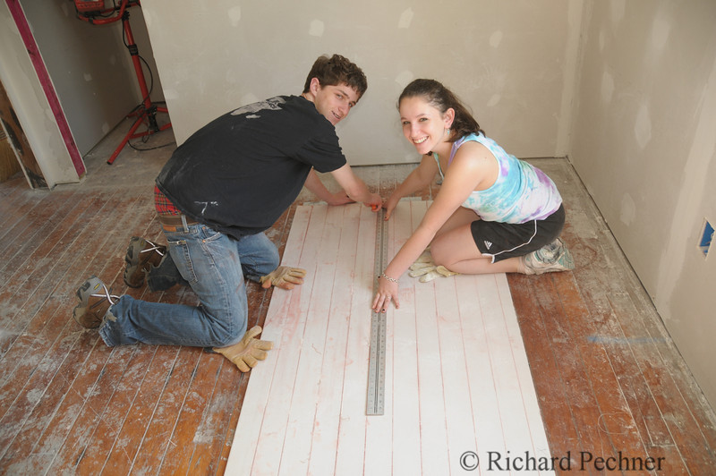 Michael and Sofi measuring a piece of sheet rock to cut up to case the windows.
