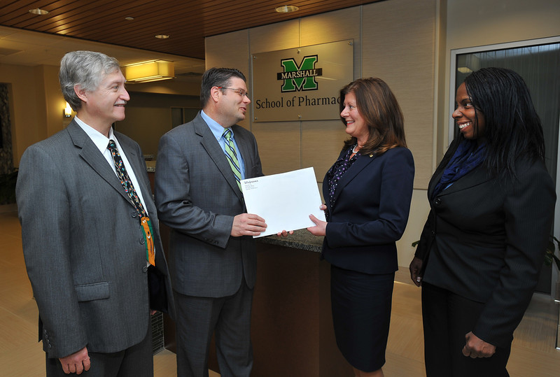 Dr. H. Glenn Anderson (second from left), associate dean of academic and curricular affairs, accepts a diversity grant packet from Dr. Debra Harris, pharmacy supervisor, Walgreens. Also pictured are Dr. Robert Stanton, assistant dean, Office of Experiential Learning (left), and  Dr. Shelvy Campbell, director of diversity (right).