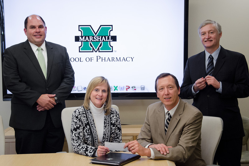 Dr. Kevin Yingling, dean of the School of Pharmacy, seated, accepts a gift from Lynne Fruth, president and chairman of the board with Fruth Pharmacy.  Also pictured are, left, Craig Kimble, Pharm. D., Director of Pharmacy and Clinical Services for Fruth, and Robert Stanton, M.B.A., Pharm.D., Director of Experiential Learning, Marshall School of Pharmacy.