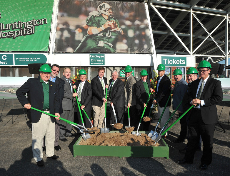 Marshall President Dr. Stephen J. Kopp, center, leads a large group in a ceremonial groundbreaking for the university's new soccer complex this afternoon outside Joan C. Edwards Stadium. To Kopp's right is Mike Hamrick, Marshall's Director of Athletics, and to Kopp's left is Chad Pennington, co-chair of Marshall's Vision Campaign.