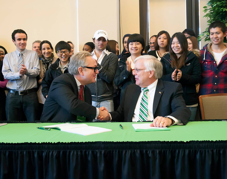 Andrew Colin, left, chairman of INTO University Partnerships, and Marshall President Dr. Stephen J. Kopp shake hands after signing an agreement Nov. 15 that is expected to build the institution's global profile and increase international student enrollment at the university.