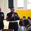 Cpt. Steven Dodson, left, listens as Sgt. Victor Arroyo, coordinator of the Toys for Tots campaign, talks with St. Joe students about the campaign. Photo by Liu Yang/Marshall University.