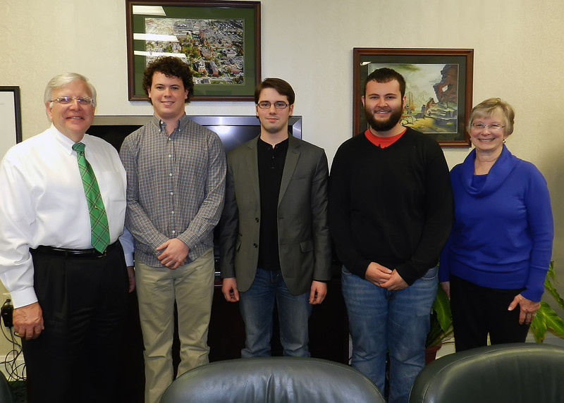 From left, President Stephen J. Kopp is joined by students Kyle Mullins, Bradley Leonard and Tyler Vance, along with Jane Kopp, in a photo Monday in the president's office.  Leonard took first place, Vance was second and Mullins was third in the Digital Card division of the President's Holiday Design Contest.