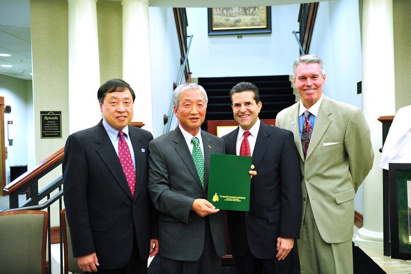From left, Dr. Haiyang Chen, dean of Marshall's College of Business; Dr. Chong Kim, former dean of the College of Business for whom the Dr. Chong W. Kim Endowed Scholarship is named; Norman Mosrie, president of the Advisory Board of the College of Business at Marshall; and Lance West, vice president for development at Marshall, pose with a copy of the guidelines for the Kim scholarship. Photo by Liu Yang/Marshall University.