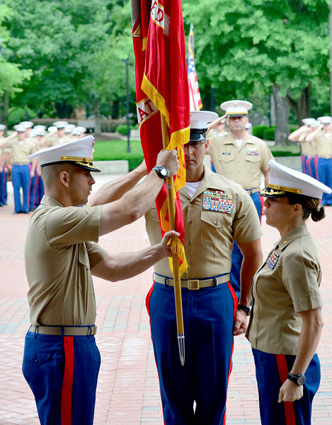 Maj. Gabriel Diana, left, holds the U.S. Marine Corps flag after receiving it from Maj. Lauren Edwards, right, in today's change of command ceremony at Marshall University. Edwards relinquished command of Recruiting Station Charleston to Diana in the ceremony June 26.