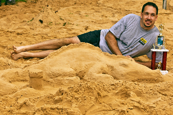 """TJ Cooley poses for a family photo in front of 'Cenzo Dragon', hs winning entry in the sand sculpture contest held at the """"Last Splash"""" at the Highlands Park Pool held Saturday July 31, 2010 in Westerville, Ohio.  The pool closed early for the season for a complete demolition and re-construction.  The new facility is expected to open on Memorial Day 2011."""