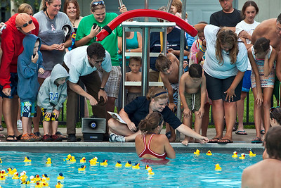 """Megan Nielsen, sitting cross legged, keeps watch over ducks swimming across the pool to determine the winner in a giveaway of season passes during the """"Last Splash"""" at the Highlands Park Pool held Saturday July 31, 2010 in Westerville, Ohio.  The pool closed early for the season for a complete demolition and re-construction.  The new facility is expected to open on Memorial Day 2011."""