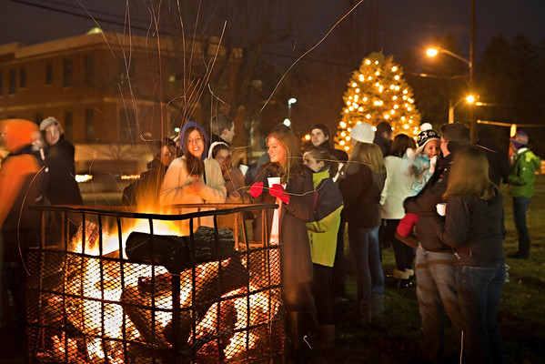 Students and faculty warms themselves next to the bonfire at the annual lighting of the Hudler Memorial Christmas tree on the campus of Ohio Wesleyan University Sunday evening December 5, 2010. About 100 people turned out for the third annual event which pays homage to OWU 1956 alumni Ron Hudler who died in 2008 and operated a christmas tree farm after a successful business career.   | ©James D. DeCamp | http://www.JamesDeCamp.com | 614-462-8027