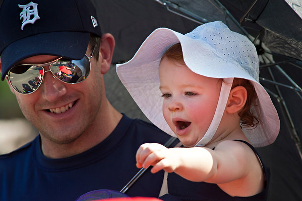 Arabella Hartings, 18 months, reaches out to wave hello to passerby's in the Worthington Memorial Day Parade held Monday May 30, 2011 on High Street in downtown Worthington.  On left is dad Joe Hartings of Worthington.