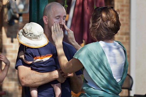 Cory Linden gets sunscreen applied to his face by his wife Stacia during the Worthington Memorial Day Parade held Monday May 30, 2011 on High Street in downtown Worthington.  In his arms is 6 month old son Tate.