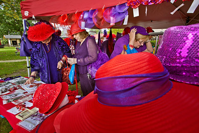 l-r: Toni Gilbert, Brenda Volpe and Anne Langella, all from Hilliard, look over a vendors wears during a gathering of the Red Hat Ladies at Weaver Park in Hilliard, Ohio Sunday afternoon September 25, 2011.  Several dozen ladies from through-out the state attended the event.