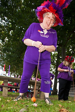 "Queen Mum Purple Aura Lucy Jamison tries her hand at ""golf"" using an orange in pantyhose as a club during a gathering of the Red Hat Ladies at Weaver Park in Hilliard, Ohio Sunday afternoon September 25, 2011.  Several dozen ladies from through-out the state attended the event."