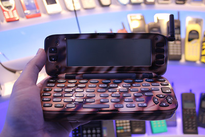 custom model of the Nokia 9000 Communicator. Among the forerunners of modern smartphones, the first communicator from 1996 flipped open to reveal a QWERTY keyboard and had the ability to send/receive faxes, email, SMS, notes, calendar, calculator, browse the (text-based) web. Also popularized by an appearance along side Val Kilmer in The Saint.