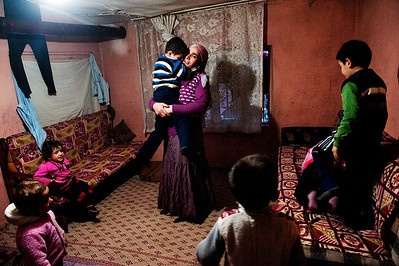 "Selcan Kesman holds her distraught son, surrounded by her children and several nieces and nephews.  Kesman shares the the tiny squatter dwelling with 3 families, 18 people in total.  Despite living in Istanbul for over ten years, the families say they are discriminated against for being Kurdish.  Feeling alone and isolated, she and her two sister-in-laws often confine themselves to the small ramshackle community they live in. The women say they feel as though integration is much harder for them than their husbands. ""We can't even ask our neighbors to watch our kids,"" said her sister in-law, Gulcan Kesman."