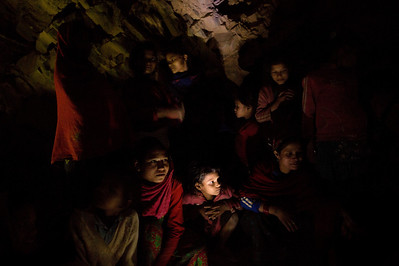 Deep in the Himalayan foothills of western Nepal, an age-old Hindu practice called chaupadi still banishes menstruating women-- considered unclean-- from their homes during their periods. Sleeping in animal sheds, caves or even out in the open, rape and deaths due to exposure and animal attack are common.  Here, a group of women and girls chat around a fire as they prepare to sleep under a rock outcropping in observance of chaupadi in Kalekanda village, Achham, Nepal, December 18, 2012.  The space, shared by all of the village women, provides no protection from the elements.