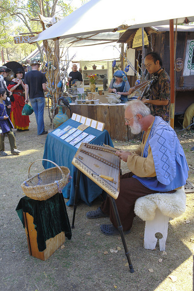 I think the instrument this guy is playing is called a dulcimer.