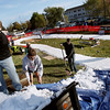 Record-Eagle/Keith King<br /> Matt Durand, from left, of Interlochen, Glenn Goodman, of Bellaire and Yensen Schwab, of Williamsburg, shovel ice from local ice rinks onto a course where cross-country skiers race against the clock Saturday, October 22, 2011 during the second annual Nordic Fest. The event includes a Vasa Ski Club membership drive and party as well as a cross-country  and telemark ski swap with the ski race being the U.S.A. Nordic, and Michigan Cup, cross country ski 2011-2012 racing season opener.