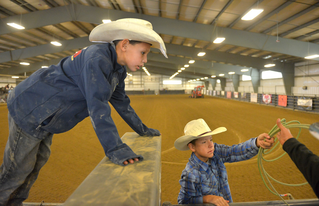 Justin Sheely | The Sheridan Press<br /> Eleven-year-old Karson Campbell, left, and Nicholas Three Irons, 9, hangout by the bucking chutes during the performance of the Northern Plains Indian Rodeo regional finals Saturday at the Sheridan College AgriPark.