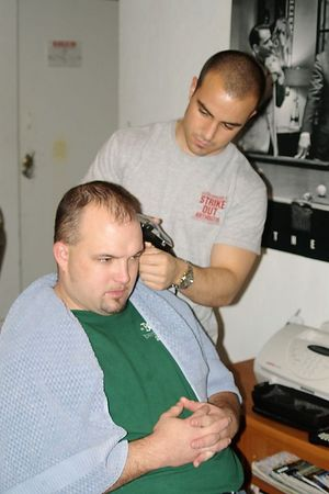 "<font size=""3"">Steve trims Eric's hair</font>"