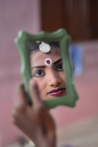 Reflections in the mirror as the young girl dancers get ready for the evening events.  The Konark Dance & Music Festival 2011 held from February, 19th to 23rd, organized by Konark Natya Mandap. The festival takes place in an open-air auditorium and enlivens the spirit of the sculptures of Konark temple which is just a short distance away.  The objectives of the Konark Natya Mandap are to preserve, promote, and project the rich cultural heritage of Orissa and to infuse cultural awareness in the minds of all. Started with painstaking efforts of internationally renowned Odissi dance teacher Guru Gangadhar Pradhan who unfortunately passed away last year. For more details on the festival see  http://www.konarknatyamandap.org/ and http://konarkfestival.com/