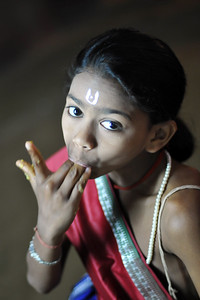 Young gotipua dancer enjoying a snack before the evening events start.  The Konark Dance & Music Festival 2011 held from February, 19th to 23rd, organized by Konark Natya Mandap. The festival takes place in an open-air auditorium and enlivens the spirit of the sculptures of Konark temple which is just a short distance away.  The objectives of the Konark Natya Mandap are to preserve, promote, and project the rich cultural heritage of Orissa and to infuse cultural awareness in the minds of all. Started with painstaking efforts of internationally renowned Odissi dance teacher Guru Gangadhar Pradhan who unfortunately passed away last year. For more details on the festival see  http://www.konarknatyamandap.org/ and http://konarkfestival.com/
