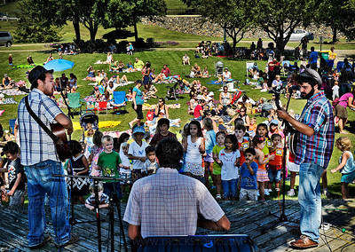 A view of the Okee Dokee Bros. playing their free 'Kids Koncert' for dozens of families from Parkers Lake Park Stage Wednesday, Aug. 17, 2011.  The band members are, left to right, Joe Mailander on acoustic guitar, Jed Anderson played a drum called a Cajon, and on banjo, Justin Lansing.