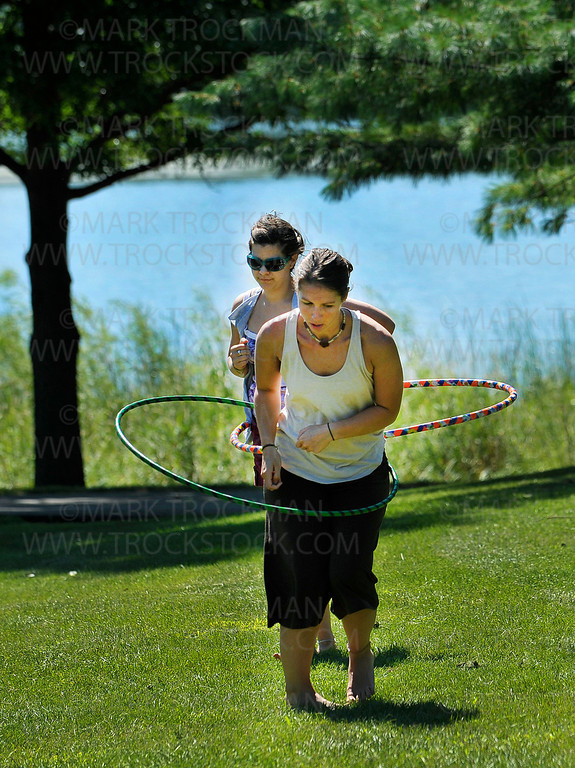 Nicole Cortese, left, Moorhead, and Shayna Connell, Fargo, heard the Okee Dokee Bros. 'Kids Koncert' music and stopped to let off some steam with their Hula Hoops in Parkers Lake Park Wednesday, Aug. 17, in Plymouth.