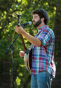 Okee Dokee Bros. band member Justin Lansing plays his banjo and sings Bluegrass tunes on the Parkers Lake Park Stage in Plymouth Wednesday, Aug. 17.