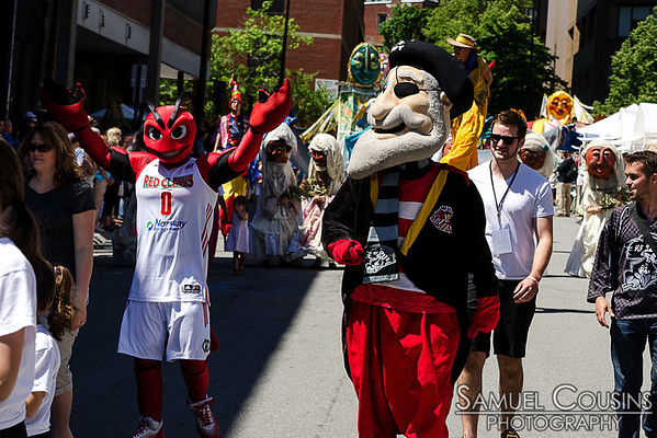 Mascots from the Maine Red Claws and the Portland Pirates marching in the Old Port Festival parade.