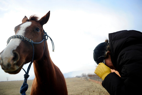 N0108FIRE450.jpg Janie Jill Toiton, of Diamond Double T Ranch, takes cover of the wind as she tries to evacuate the ranch's horses near Lake Valley Golf Course in north Boulder on Wednesday, January 7, 2008.<br /> CAMERA / KASIA BROUSSALIAN