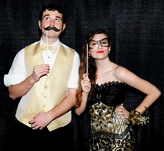 Photo courtesy of Randy Amick   TriState Studios Tyler Wachsmann (left) and Carly Wagers use props to embellish their black-and-gold prom attire.