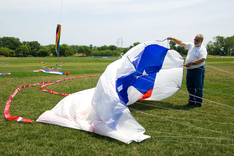 """<font size=""""3"""">Don Murphy, president of the group, is working to get this large kite aloft.</font>"""