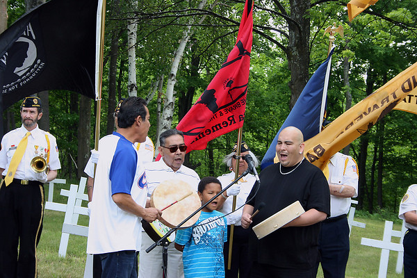 """Medicine Lodge singers Shocko Hall with drum, 8-year-old son Savante, father Wallace Hull (sunglasses) and Karman Two-Crow sign a """"traveling song"""" at the re-dedication."""