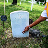Record-Eagle/Loraine Anderson<br /> Linda Woods, a member of the Eagletown Post color guard, scatters tobacco on a grave.