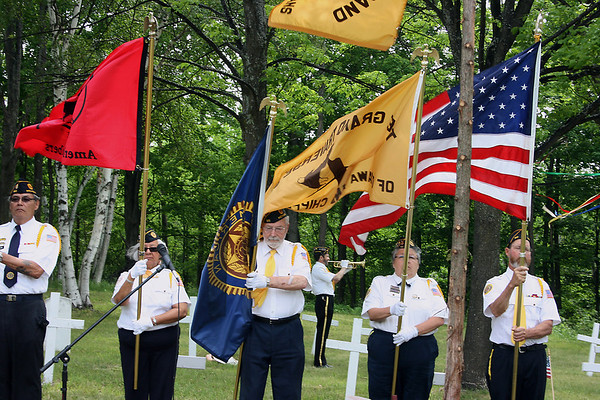 """Record-Eagle/Loraine Anderson<br /> An American Legion Eagletown Post 120 color guard stands at attention as adjutant Steve Alguires plays """"Taps"""" during the Memorial Day service at Onominese Indian Cemetery Monday, May 28."""