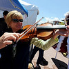 """Ann Yeager tries out the viola at the Parlando School of the Arts booth.<br /> The Twenty Ninth Street mall held the third annual Open Studios Spring Art Fair this weekend.<br /> For photos and a video of the fair, go to  <a href=""""http://www.dailycamera.com"""">http://www.dailycamera.com</a>.<br /> Cliff Grassmick / May 16, 2010"""