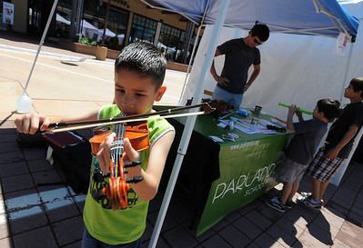 Brian Ordones, 7, tries out the violin at the Parlando School of the Arts booth. The Twenty Ninth Street mall held the third annual Open Studios Spring Art Fair this weekend. For photos and a video of the fair, go to www.dailycamera.com. Cliff Grassmick / May 16, 2010