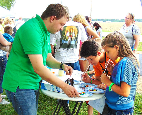 Debbie Blank | The Herald-Tribune<br /> Batesville Memorial Public Library volunteer Brad Marcy (from left) oversees a Minute to Win It game using M&Ms being played by Logan Reed, 11, Milan, and sister Tryniti, 8.