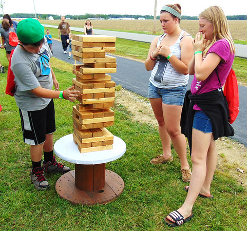 Debbie Blank | The Herald-Tribune<br /> Mark Jenkins (from left), 12, Milan, plays a giant game of Jenga with Kayla Upton, 12, Brookville, and sister Sadie, 13, at Family Fun Night June 3 in Osgood. The booth was sponsored by One Eighty Youth Ministries, Milan.
