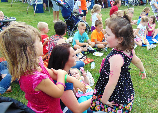 Debbie Blank | The Herald-Tribune<br /> Osgood friends Kynlee Gunter (left), 3, and Kaitlynn Shadday, 5, wait for the Silly Safaris show to begin while Kaitlynn's mom, Renae, cradles Allyson, 11 months.