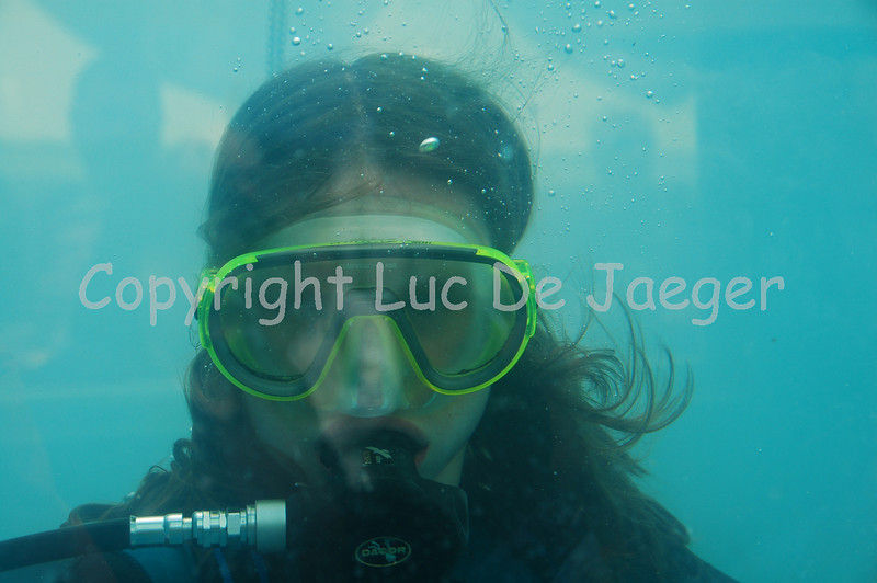 This girl demonstrates how the diving equipment and face mask work. She was in a very small container filled with water and this image is shot through the green/blue glass of the container. Shot with the Nikkor 18-200mm lens. No post processing.